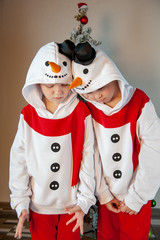 Cute boys dressed in festive costumes of Santa Claus and snowmen and decorate Christmas tree with balls and garlands. Children play and wait for gifts. Christmas Eve