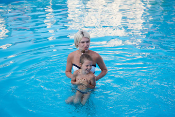 Happy mother and daughter playing in swimming pool