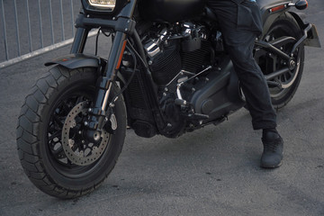 Biker in black clothes sitting on motorcycle