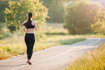 beautiful young sporty woman running on asphalt road in the Park in the morning