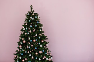 Great beautifully decorated Christmas tree with pink baubles, ribbons, snowflakes, and a lot of gift boxes and toys beneath. Over white brick background