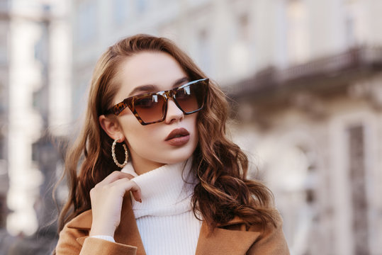 Outdoor close up portrait of young beautiful woman wearing trendy leopard print sunglasses, hoop earrings,  white turtleneck, coat, model posing in street of european city. Copy, empty space for text
