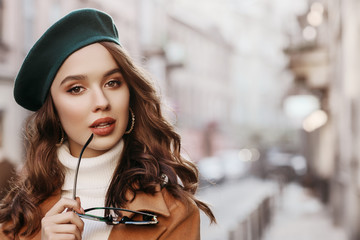 Outdoor close up portrait of young beautiful woman with long hair wearing stylish autumn clothes, green beret, holding sunglasses, model posing in street of european city. Copy, empty space for text Wall mural