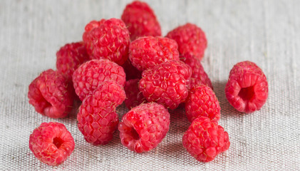 Macro of fresh ripe raspberries on the textile background in rustic style