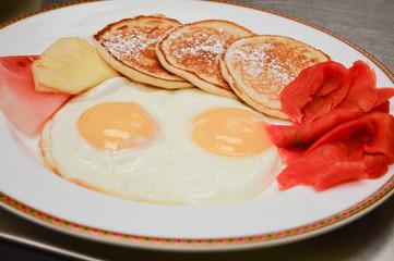 eggs, pancakes, salmon and fruit breakfast