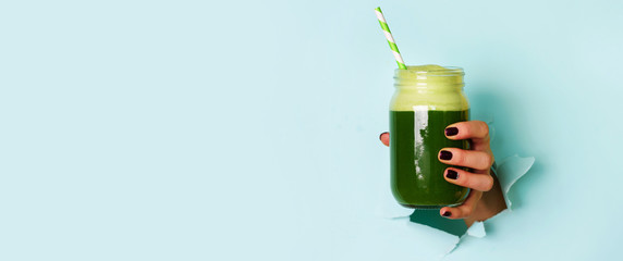 Woman hand holding glass jar of green smoothie, fresh juice against blue background. Healthy beverage, vegan, vegetarian concept. Banner with copy space