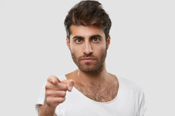 You should listen me carefully! Strict unshaven man with serious facial expression, points directly at camera with index finger, wears casual clothes, models against white background, choose someone