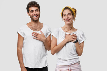 Indoor shot of pleased woman and man keep hands on chest and smile broadly, express gratitude to relatives for help, stand closely to each other, isolated over white background. Appreciation concept