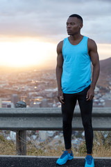 Full length shot of sporty man wears activewear, poses on top with panoramic beautiful view, enjoys sport training early in morning, nice sunrise in background, has contemplative expression.