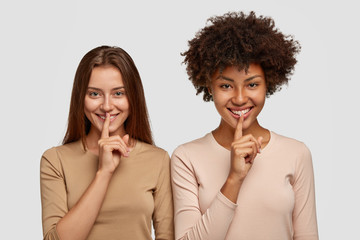 Indoor shot of positive funny multiethnic women show silence sign, ask someone be quiet, spread rumors around, have happy expressions, dressed in casual clothes, isolated over white background