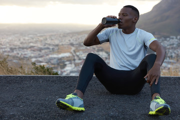 African American man drinks fresh water from bottle, rests on asphalt, sits against mountain background outdoor, feels relaxed, dressed in casual t shirt, sneakes and trousers. Relaxation concept