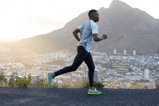 Self determined dark skinned sporty male runner wears sportclothes, runs on long distance across mountain road, enjoys fresh air, feels energetic and motivated. People, lifestyle and sport concept
