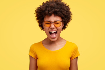 Displeased dark skinned emotional African American woman screams loudly, opens mouth, wears trendy sunglasses and casual t shirt, isolated over yellow background. Monochrome. Frustration concept