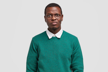 Studio shot of handsome dark skinned male frowns face in displeasure, doesnt like idea for project work, wears stylish green sweater, isolated over white background. Black dissatified hipster