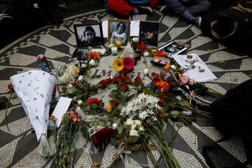 Pictures of former Beatle John Lennon are seen among flowers and candles at the Imagine mosaic in the Strawberry Fields section of New York's Central Park to mark the 38th anniversary of his death, in New York