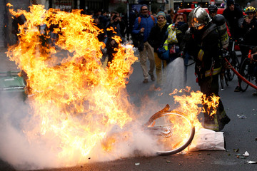 """A fireman extinguishes a burning bicycle during clashes with yellow vests protesters as part of a national day of protest by the """"yellow vests"""" movement in Paris"""