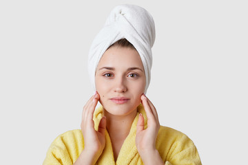 Skin care concept. Close up shot of attractive young lady has flawless skin, wears white towel on head and yellow bathrobe, models over white background, demonstrates natural beauty. Hygiene