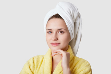 Portrait of pleasant looking Caucasian woman holds hand under chin, has healthy skin, looks at camera, dressed in domestic clothes, relaxed after shower, isolated over white background. Beauty concept