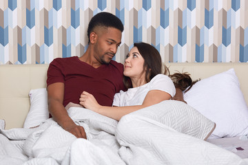 Photo of multiethnic married young woman and man cuddle and look at each other with love, enjoy calm domestic atmosphere at home, pose at bed, have lazy day off. People, rest, spare time concept