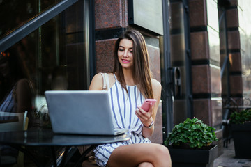 Young pretty woman in street cafe with tablet laptop