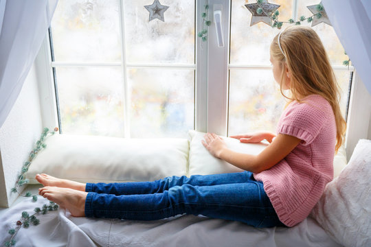 Little girl sitting on windowsill at home and looking out window in beautiful christmas day. Happy New year