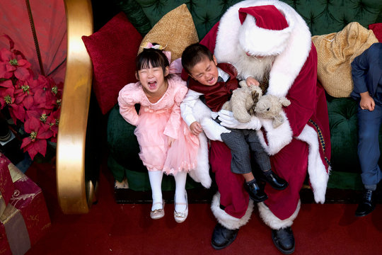 A girl laughs while her brother cries being held by Santa Claus at the King of Prussia Mall, in King of Prussia,