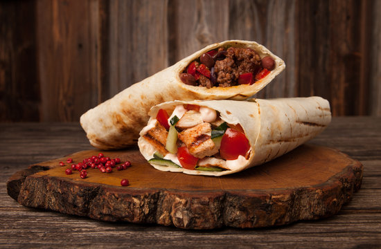 Burrito and shawarma wraps with beef and pork vegetables on wooden table. Copy space for text.