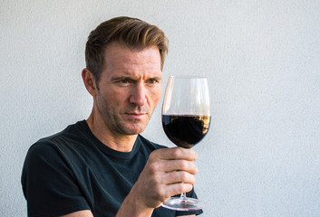 handsome Caucasian man holding a glass of red wine