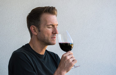 handsome Caucasian man with his eyes closed savoring a glass of red wine