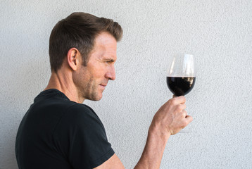 profile of a handsome Caucasian man holding a glass of red wine