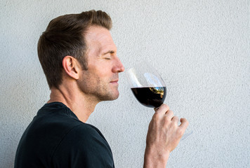 profile of a handsome Caucasian man with his eyes closed savoring a glass of red wine
