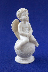 Sitting, on a round stone, an angel with wings, on a background of blue fabric