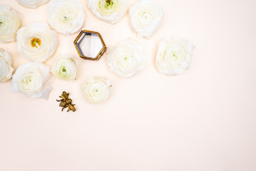 White Ranunculus flower flat lay on blush background with glas jewelry box