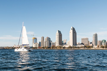 A sailboat passes by the downtown San Diego skyline.