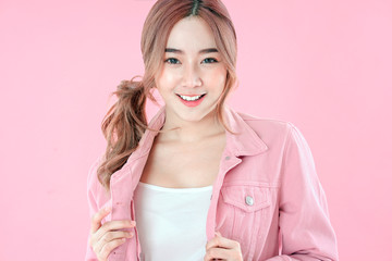 Asian woman with pigtail hair, jeans jacket clothing with backpack, pink background