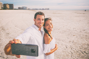 Phone selfie photo portrait couple happy on summer vacation travel tropical caribbean beach destination taking mobile phone picture of honeymoon.