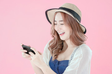 Asian woman play mobile game on smartphone, summer holiday clothing, pink background