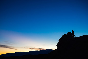 Silhouette of a photographer leaning against a boulder at sunset