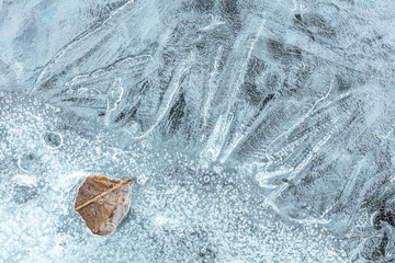 Frost patterns on ice surface. River covered with ice. Texture background