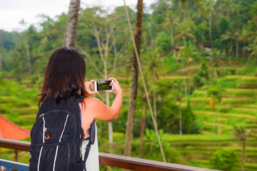 young happy backpacker woman enjoying holidays trip taking photo with mobile phone of tropical jungle and rice terrace view carrying backpack in tourist travel