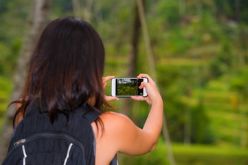 young happy backpacker woman enjoying holidays trip taking picture with mobile phone of tropical jungle and rice terrace view carrying backpack in tourist travel