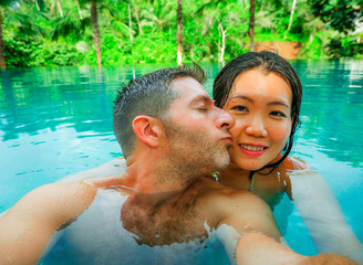young happy and beautiful mixed ethnicity couple Asian woman and Caucasian man taking romantic selfie picture at tropical resort swimming pool enjoying honeymoon trip