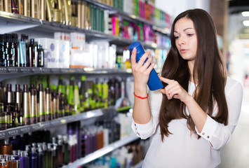 Girl attentively choosing haircare products at cosmetics store
