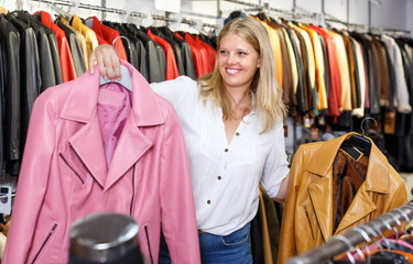 Portrait of active woman customer with leather jackets in store