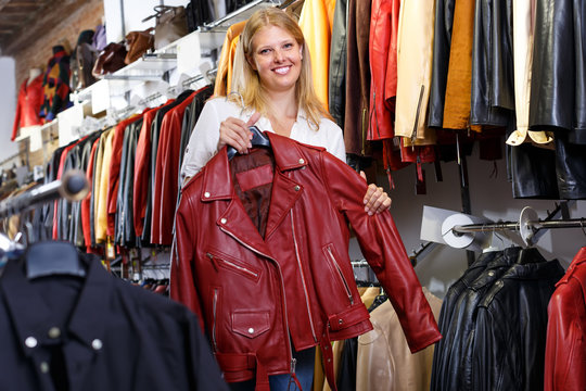 Portrait of happy female customer with leather jackets in store