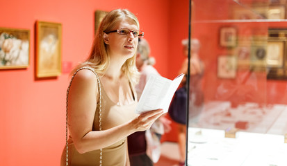 Woman holding brochure in museum of arts