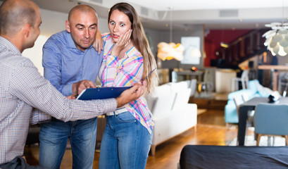 Couple shocked from looking through price-list