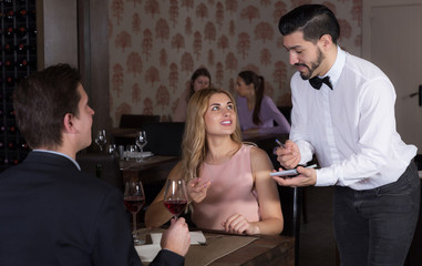 waiter taking order from couple in restauran