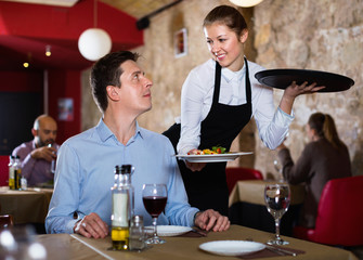 Polite waitress serving ordered dishes to smiling man at restaurant