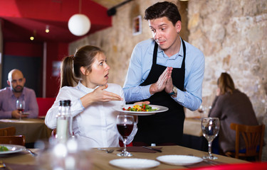 Displeased young woman conflicting with apologetic waiter because of poor quality of dish